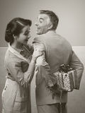 A surprise gift for her. Vintage romantic couple at home, he is giving to his wife a beautiful surprise gift Stock Image