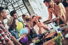 Surprise!. Group of happy people celebrating birthday among friends and smiling while having a dinner party royalty free stock image