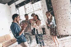 Surprise! Happy young man celebrating birthday among friends while standing in room with confetti flying around stock image