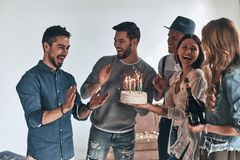 Surprise! Happy young man gesturing and smiling while celebrating birthday among friends royalty free stock photo