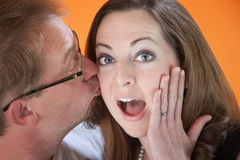 Surprise Kiss. Man surprises young woman with a kiss on the cheek Royalty Free Stock Photography