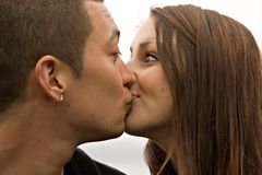 Surprise Kiss Young Couple. Young multi-racial attractive couple surprise kiss on the lips Stock Photo