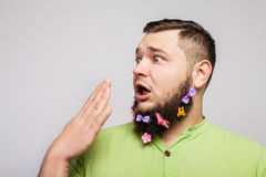 Surprise man with hair clips. Surprise man portrait with hair clips on long curly beard over white background Stock Photo