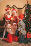 Surprise For Mom. Cute sister and brother holding present for surprise their mother for Christmas at the home. Selective focus Royalty Free Stock Image