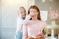 Surprise for mother. Cute child covering her mother eyes before surprise stock image