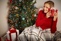 Surprise. Portrait of smiling girl holding red giftbox by her ear with decorated xmas tree near by Royalty Free Stock Images