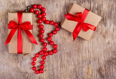 Surprise with a red bow and a necklace of coral on the old wooden background. Stock Photography