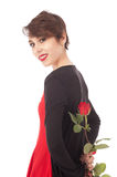 Surprise with a rose. A yong woman holds a rose at her back and is smiling gently Royalty Free Stock Photography