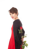Surprise with a rose. A yong woman holds a rose at her back and is smiling gently Stock Image