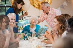 Surprise Senior Birthday Party. Senior women is overwhelmed with emotion as she is surprised with a birthday party by her friends and family Stock Photography