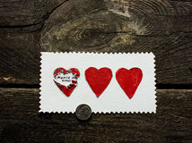 Surprise of three hearts on a wooden background on Valentine`s Day Stock Images