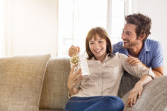 Surprise for you my love. Gift, sofa, home, girlfriend, couple. A men offering a surprise present to his wife at home Stock Photo