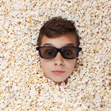 Surprise young boy in stereo glasses looking out of popcorn Stock Photos