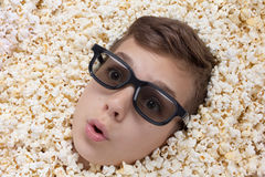Surprise young boy in stereo glasses looking out of popcorn Stock Image