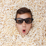 Surprise young boy in stereo glasses looking out of popcorn royalty free stock image