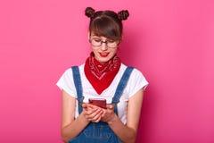 Surprised удовлетворяло милые женские печатая сообщения по ее телефону, наблюдая видео, имеющ пуки на ее голове, нося джинсовую т стоковая фотография