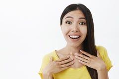 Surprised услаженная привлекательная женщина с волосами lond темными держа ладони на комоде задыхаясь и усмехаясь от признательно стоковое изображение