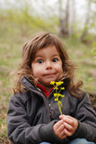 Surprised. Portrait of girl with surprised expression sat in countryside holding yellow flower royalty free stock photos