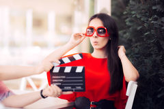 Surprised Actress with Oversized Sunglasses Shooting Movie Scene. Diva in red dress and big shades starring in an artistic film Stock Image