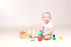 Surprised adorable baby boy sitting on the floor and playing with his toys. stock photos