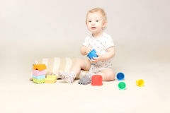 Surprised adorable baby boy sitting on the floor and playing with his toys. Studio shot of surprised adorable baby boy sitting on the floor and playing with stock photo