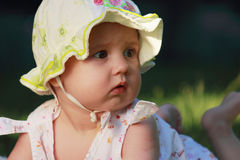Surprised adorable baby on green grass Stock Image