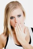Surprised afraid girl covering mouth with hand. Body language and emotions. Surprised afraid blonde girl shocked young woman covering mouth with hand Stock Photo