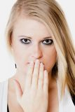 Surprised afraid girl covering mouth with hand. Body language and emotions. Surprised afraid blonde girl shocked young woman covering mouth with hand isolated on Royalty Free Stock Photos