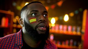 Surprised african-american man with spanish flag on cheek watching bed news royalty free stock images