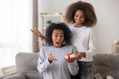 Surprised African American mother receiving gift from teenage daughter. Surprised African American mother receiving gift box from teenage daughter, smiling teen royalty free stock photo