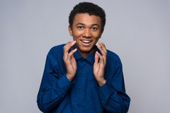 Surprised African American teenager is agitated. By something. Isolated on gray background. Expression of surprise stock images
