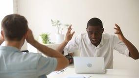 Surprised african-american winner won online looking at laptop in office stock footage