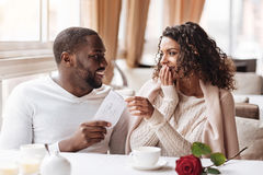 Surprised African American woman receiving a present from her boyfriend. Long awaited surprise. Cheerful delighted surprised African American women sitting in Royalty Free Stock Images