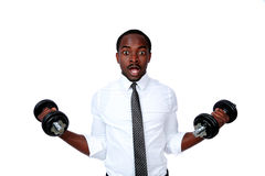 Surprised african businessman lifting dumbbells Royalty Free Stock Images