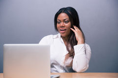 Surprised african businesswoman using laptop. Over gray background Royalty Free Stock Photo