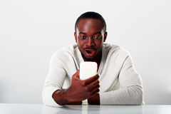 Surprised african man sitting on the table. And looking at smartphone Royalty Free Stock Photos
