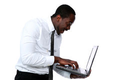 Surprised african man standing. And using laptop over white background Royalty Free Stock Images