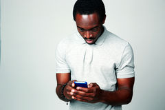 Surprised african man using smartphone Royalty Free Stock Photos