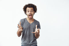 Surprised africn man with opened mouth looking at camera gesturing over white background. Royalty Free Stock Photos