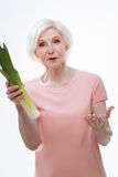 Surprised aged woman holding leek in right hand Royalty Free Stock Photo