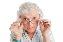 Surprised and amazed. Happy surprised old senior lady looking through her eyeglasses isolated on white background Stock Images