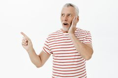 Surprised and amused expressive good-looking senior bearded male with grey hair in striped cute t-shirt gasping amazed. Touching cheek looking and pointing at royalty free stock photography