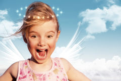 Surprised Angel. Little girl as an angel with blue sky and clouds background Royalty Free Stock Image