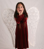 Surprised angel. Little girl dressed in angel wings holding her hands to her face in surprise Stock Images