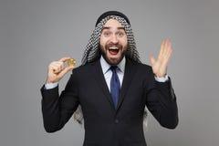Surprised arabian muslim businessman in keffiyeh kafiya ring igal agal black suit isolated on gray background