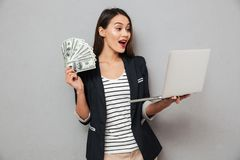 Surprised asian business woman holding money and laptop computer Royalty Free Stock Photography