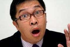 Surprised asian businessman. A surprised expression on an asian businessman of chinese descent.  Wearing squarish spectacles, business attire and dark coat. Hand Royalty Free Stock Photo