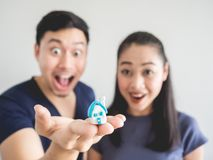 Surprised couple with small house in hand. Surprised Asian couple lover. Man show the small house in hand Royalty Free Stock Photos