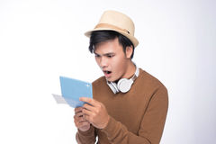 Surprised asian male tourist holding passport over grey backgrou Stock Photos