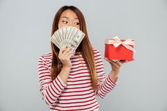 Surprised asian woman in sweater hiding behind a money Royalty Free Stock Photography